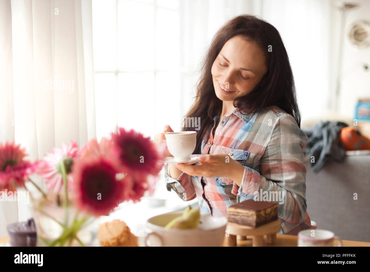 Happy girl with a mug of fragrant coffee in hands. Good breakfast at home in the living room by the window. Free space for text. - Stock Image
