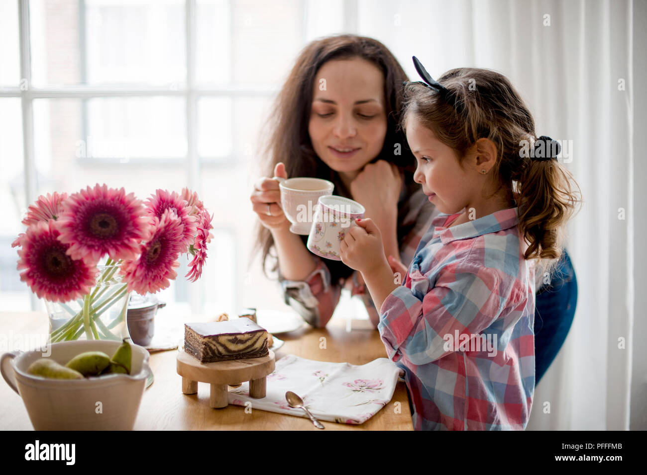 A woman and a little daughter are eating breakfast at home at a table by the window. Happy family and breakfast. Good morning at home. Free space for text. - Stock Image