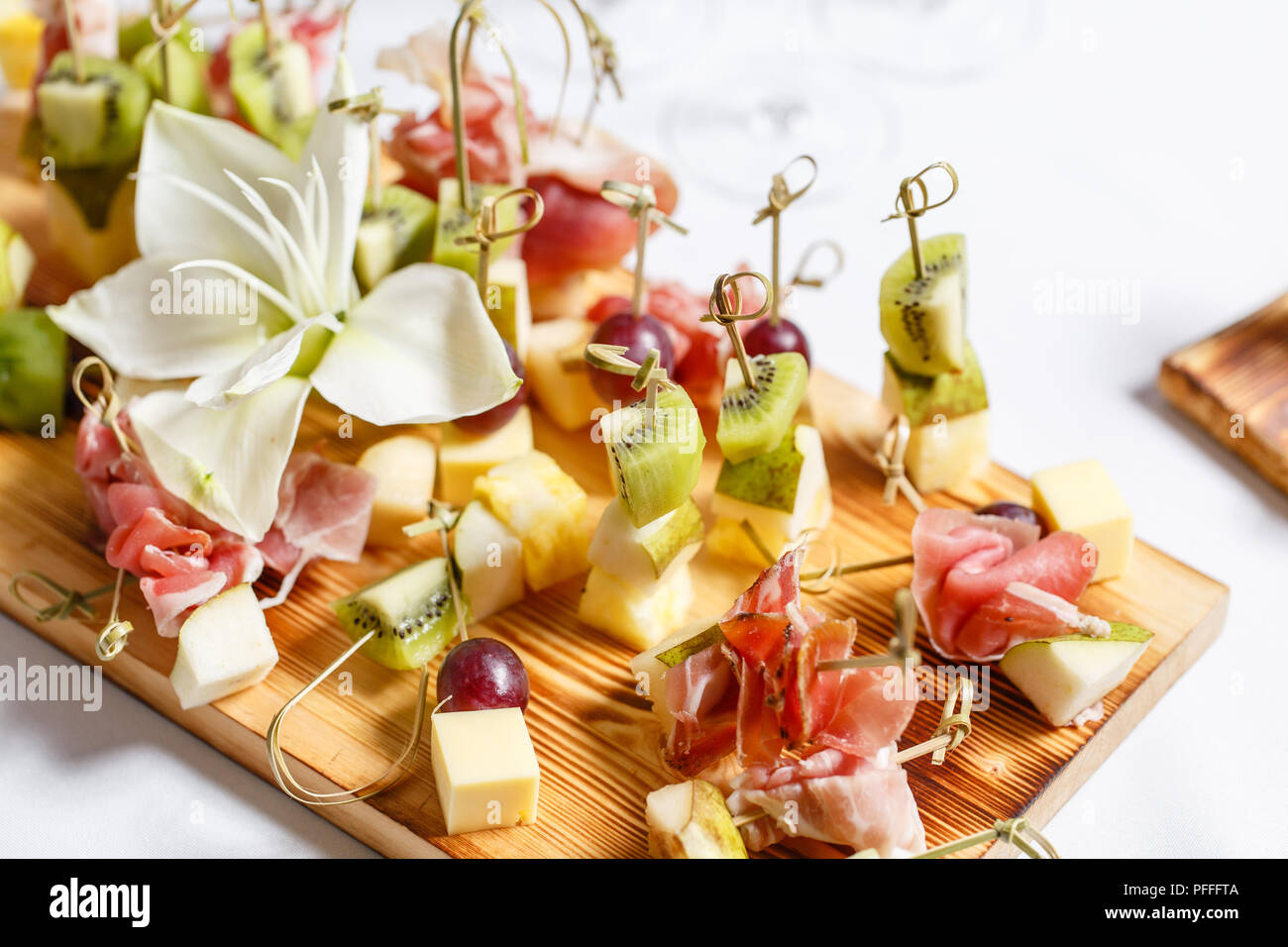 solemn happy new year banquet. Lot of glasses champagne or wine on the table in restaurant. buffet table with lots of delicious snacks. canapes, bruschetta, and little desserts on wooden plate board Stock Photo