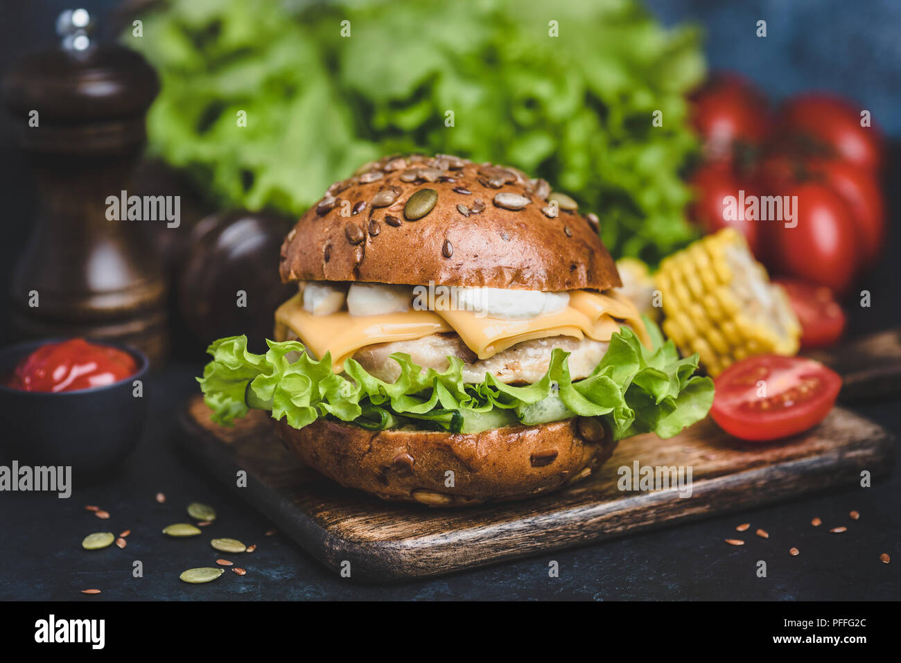 Tasty Chicken Burger On Wooden Serving Board. Cheeseburger With Cheese, White Sauce, Lettuce, Tomatoes. Closeup view, Selective focus - Stock Image