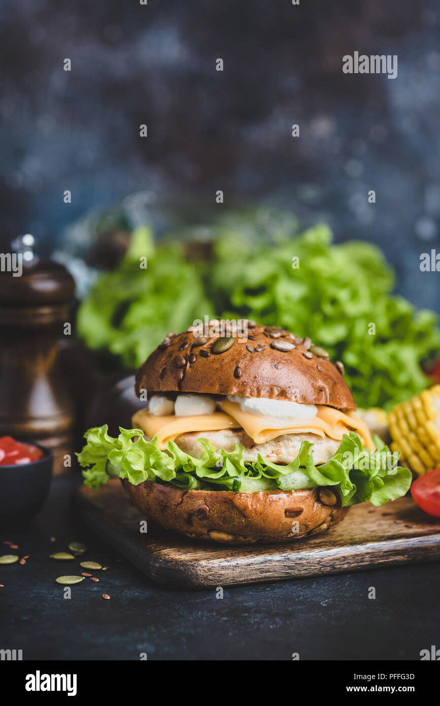 Tasty Chicken Burger With Cheese, Sauce, Lettuce On Wooden Serving Board. Closeup view, Selective focus Stock Photo