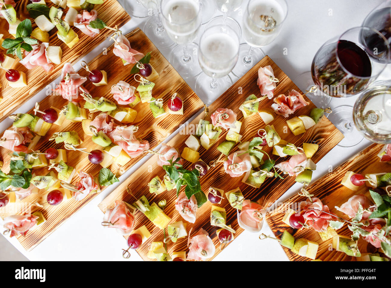 solemn happy new year banquet. Lot of glasses champagne or wine on the table in restaurant. buffet table with lots of delicious snacks. canapes, bruschetta, and little desserts on wooden plate board - Stock Image