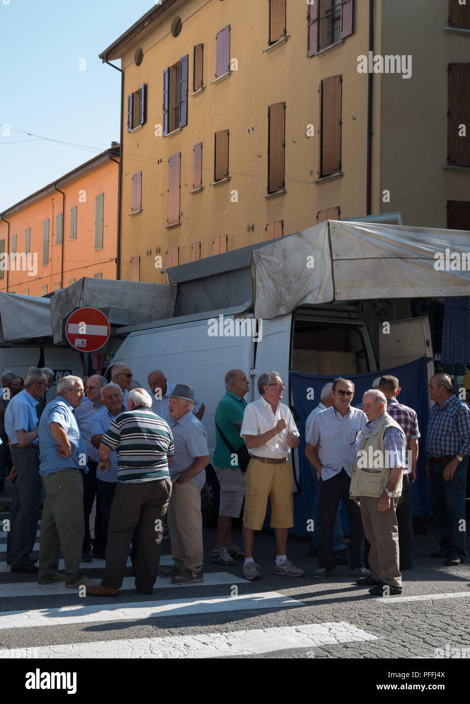 Old men gathering by busy street for a chat on market day in the small city of Castel San Pietro Terme, Metropolitan City of Bologna, Italy, Europe. - Stock Image