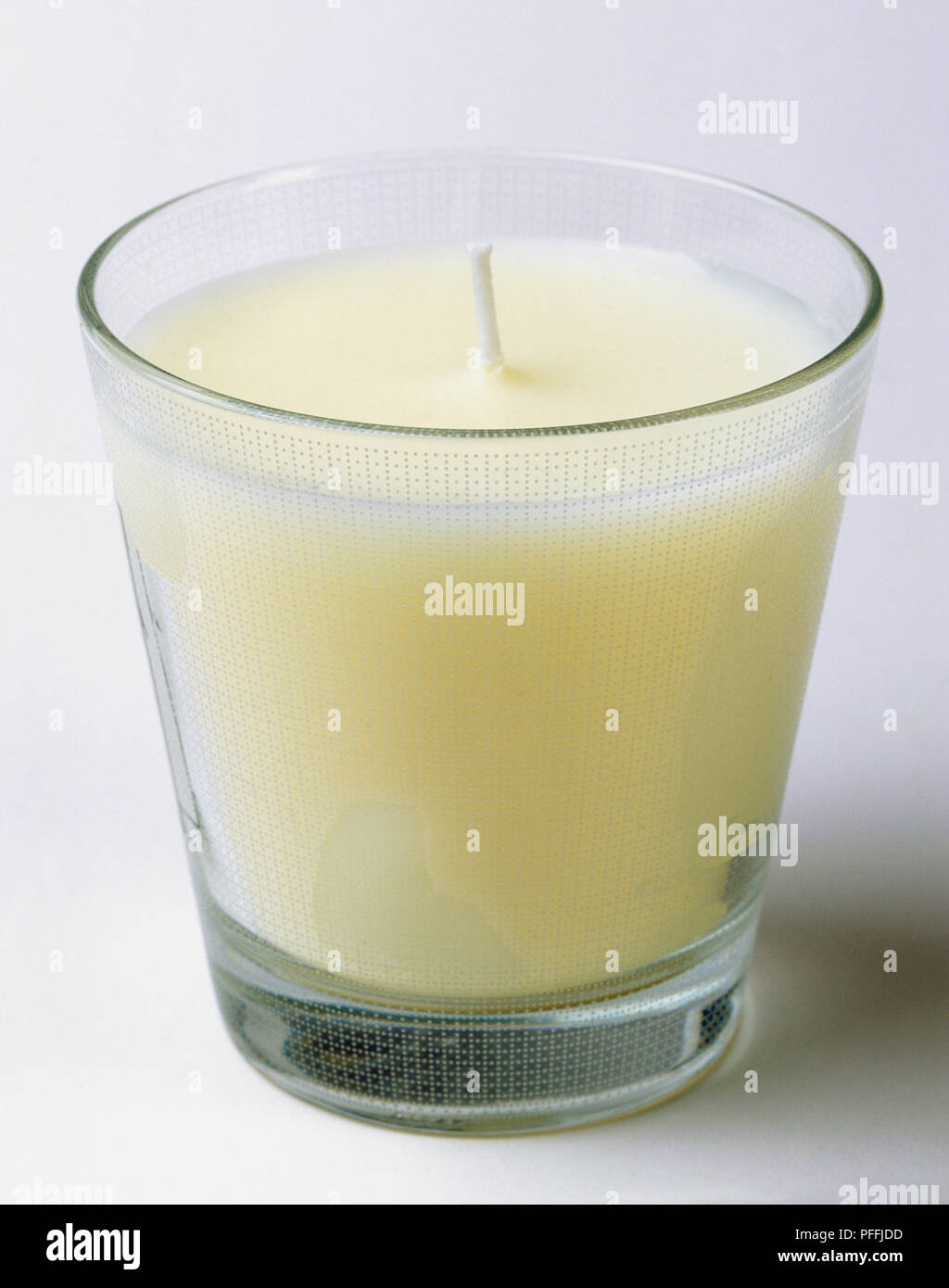 Scented candle in a glass holder, unlit wick, angled front view. - Stock Image