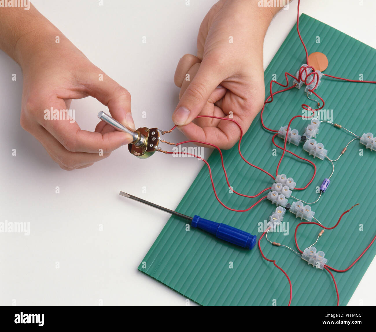 Boys Hands Attaching Wires From Connectors To Terminals Of Variable Resistor Circuit Building A Radio Close Up