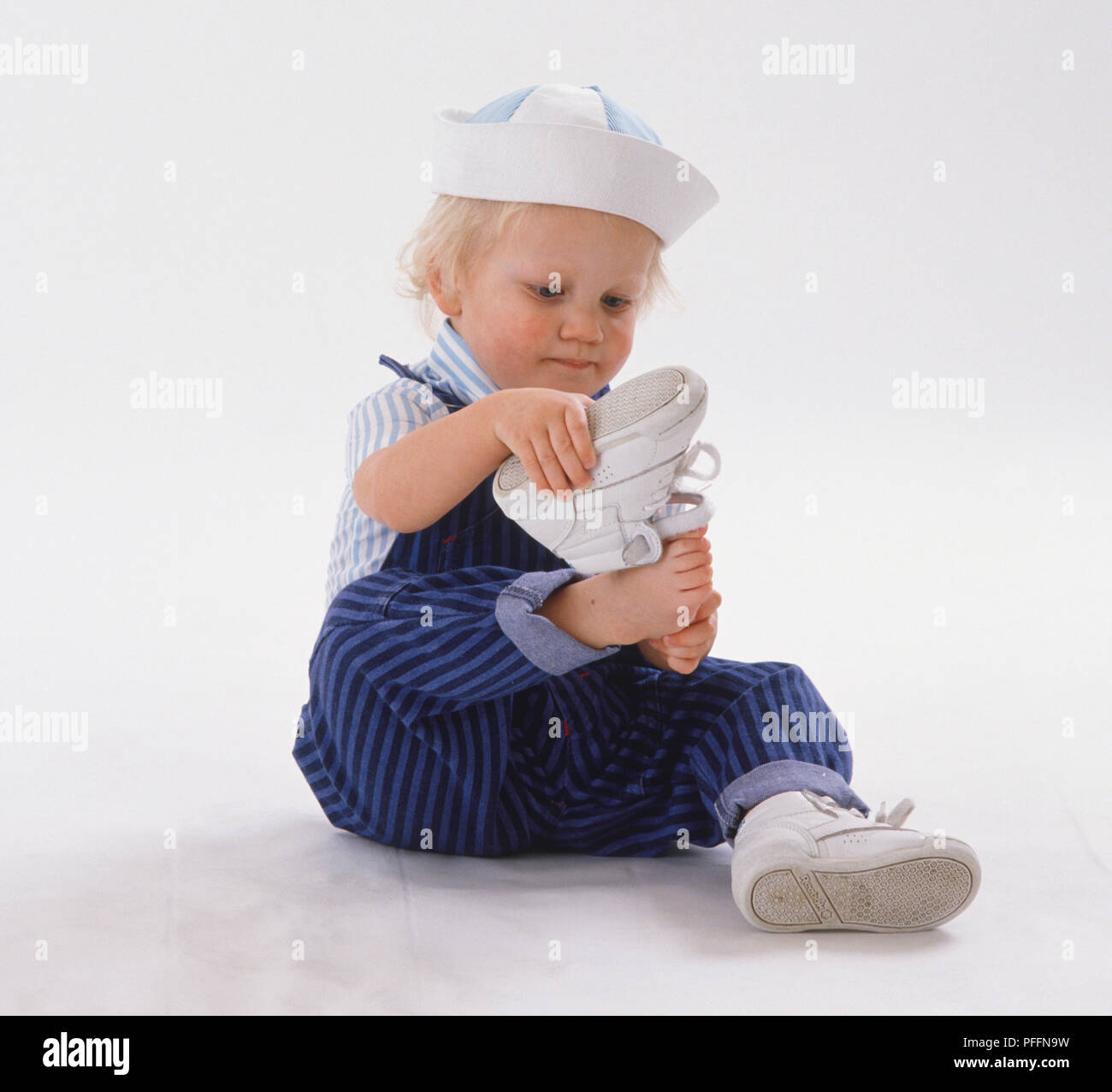 eb60ead7 Toddler wearing striped dungarees, hat and one shoe, trying to put other  shoe on, expression of deep concentration.