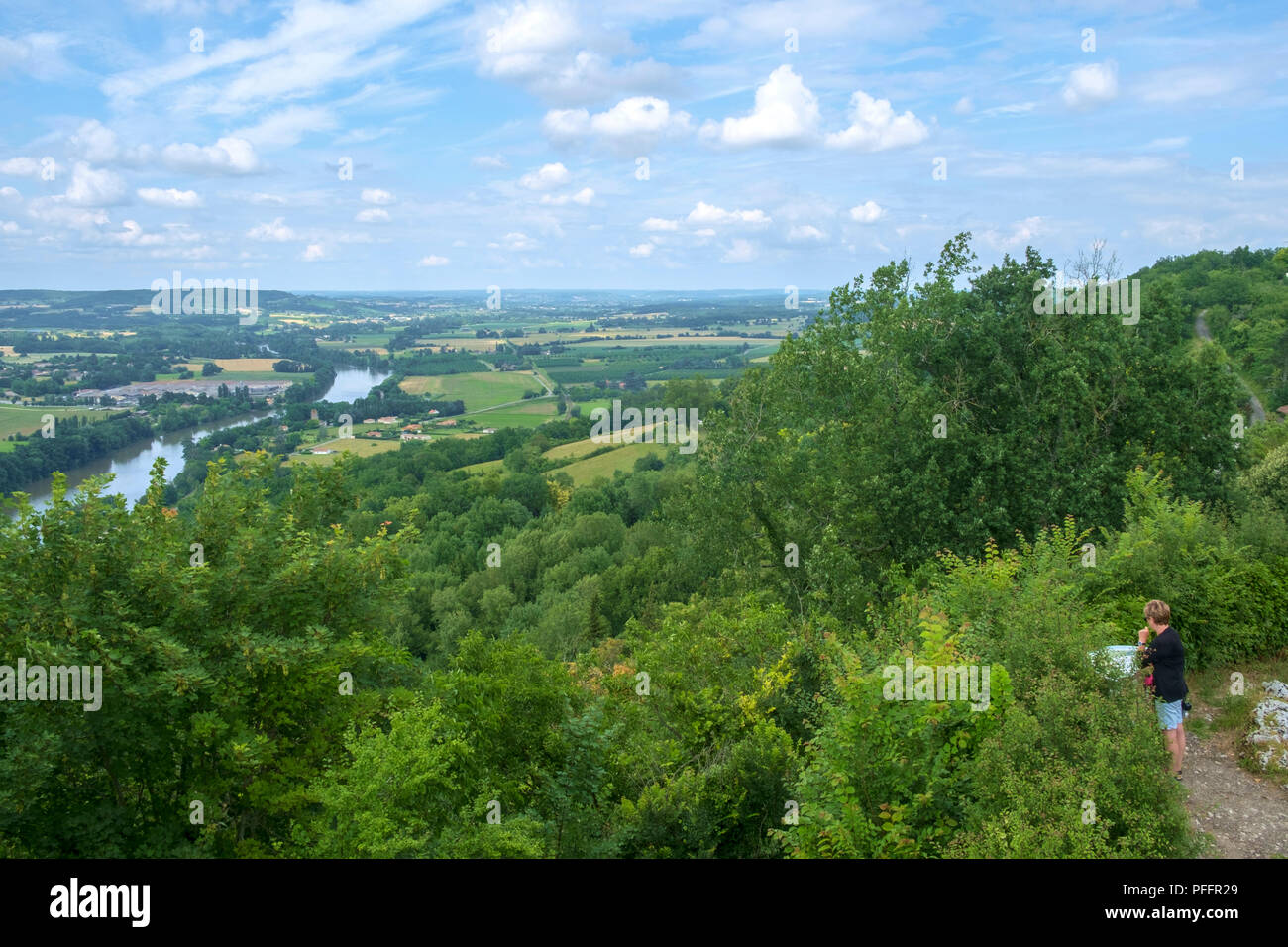 Penne d'Agenais, France - 14th June 2018: In early summer sunshine a woman considers the view over the Lot River and Valley from hilltop Penne d'Agenais  in rural Lot et Garonne, France - Stock Image