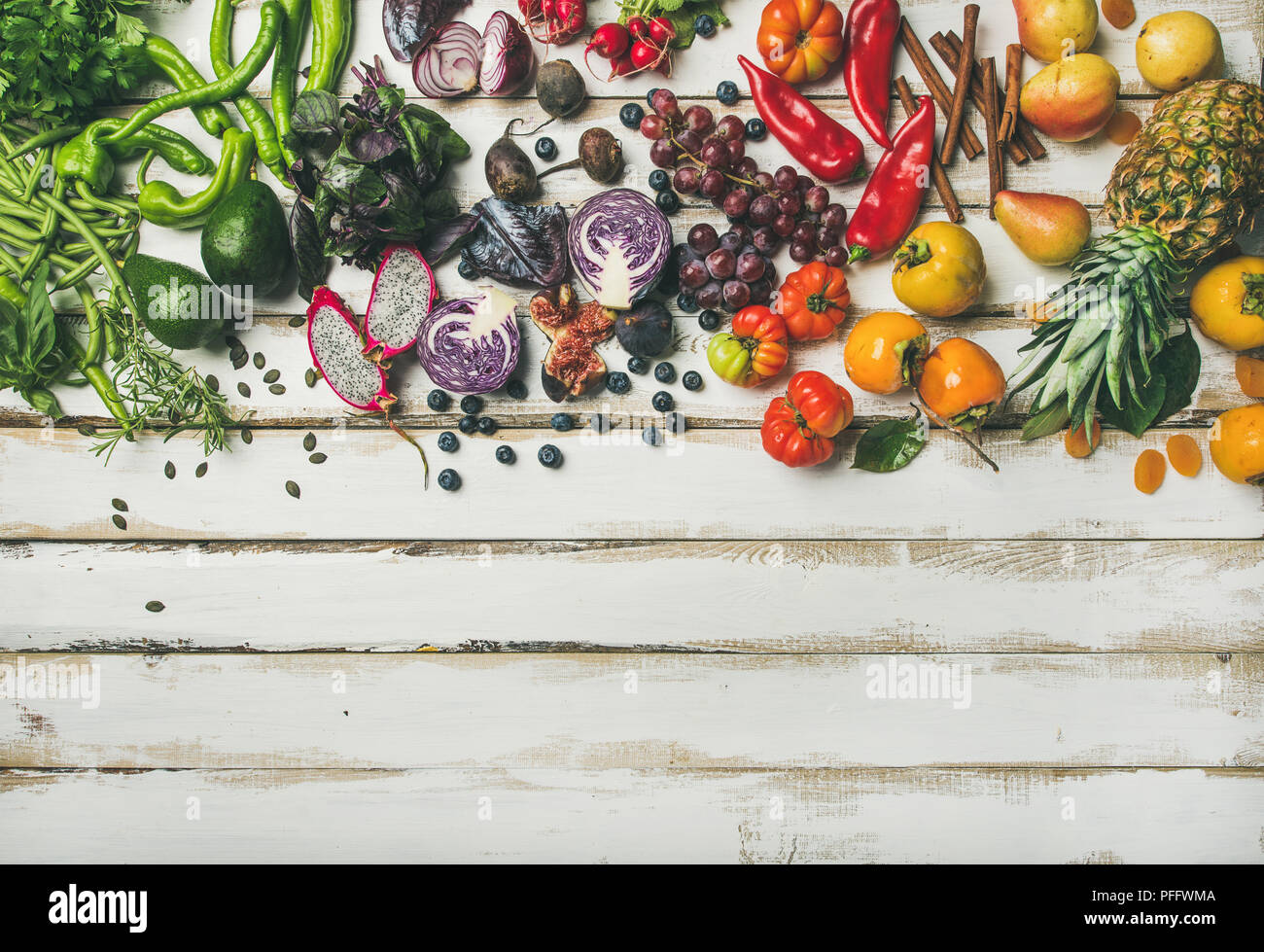 Helathy raw vegan food cooking background. Flat-lay of fresh fruit, vegetables, greens and superfoods over white wooden table, top view, copy space. C - Stock Image