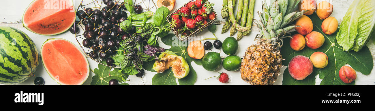 Seasonal fruit, vegetables and greens over white wooden background Stock Photo