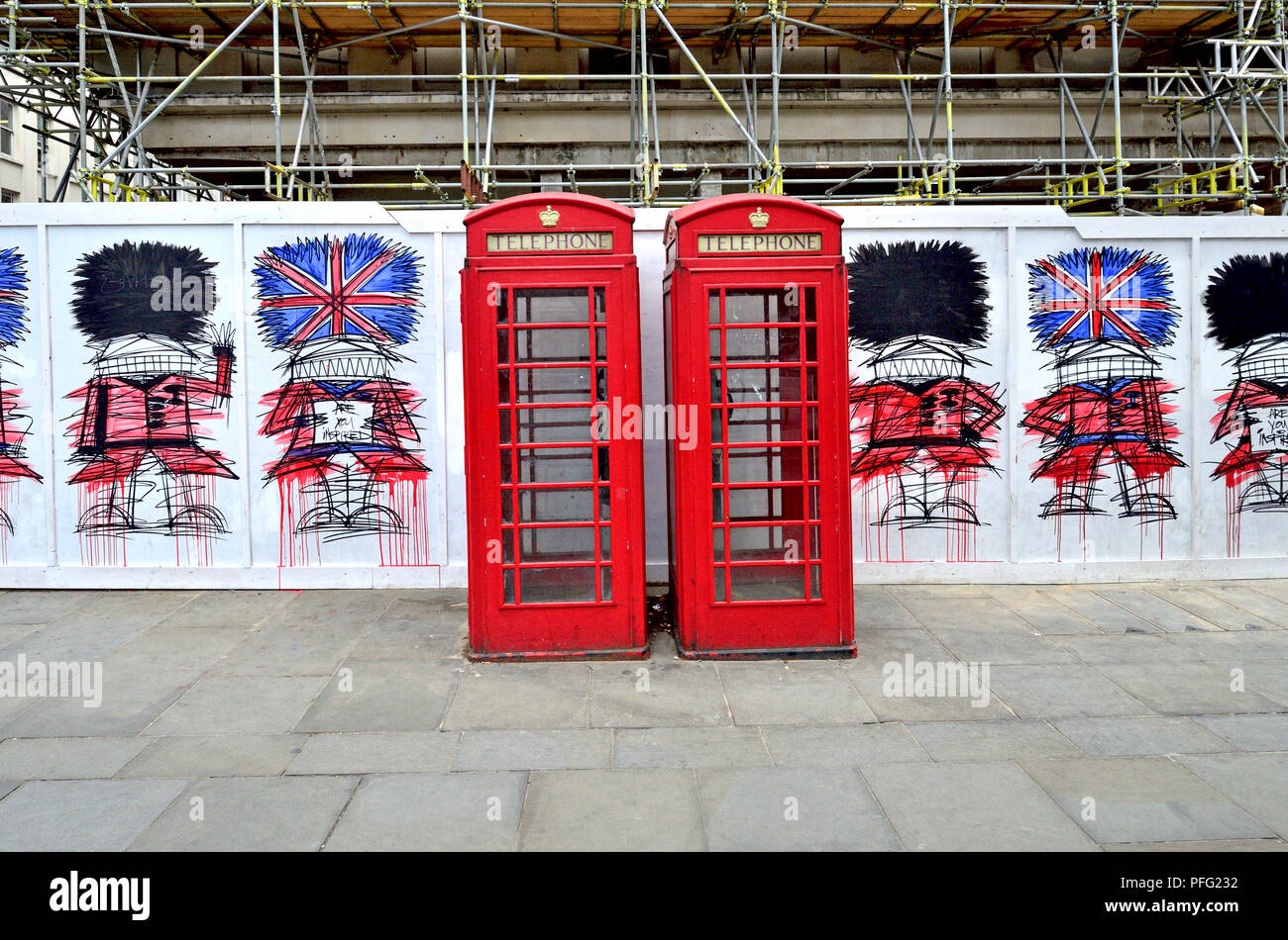Red telephone boxes and graffiti guardsmen (by Nathan Bowen) in St Martin's Place, London, England, UK. - Stock Image