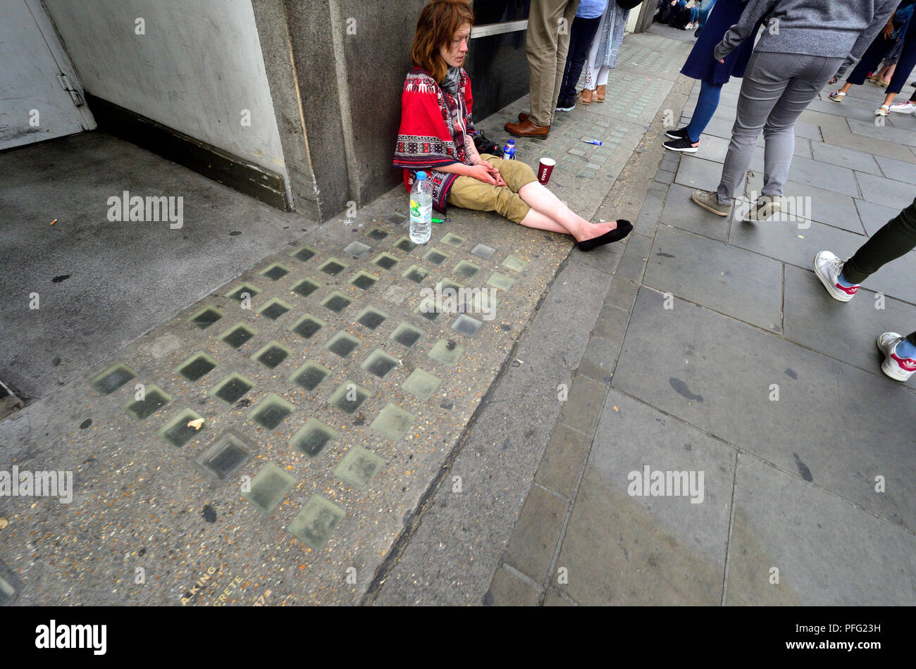 Homeless woman on the pavement in the Strand, London, England, UK. - Stock Image
