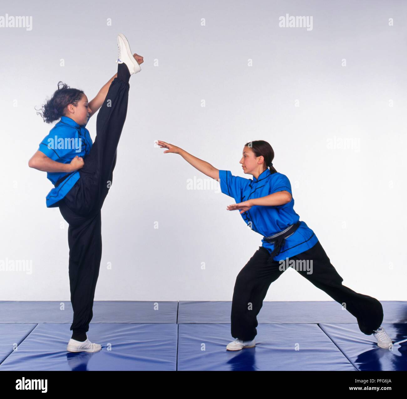 Girl performing axe kick, opponent stepping back Stock Photo