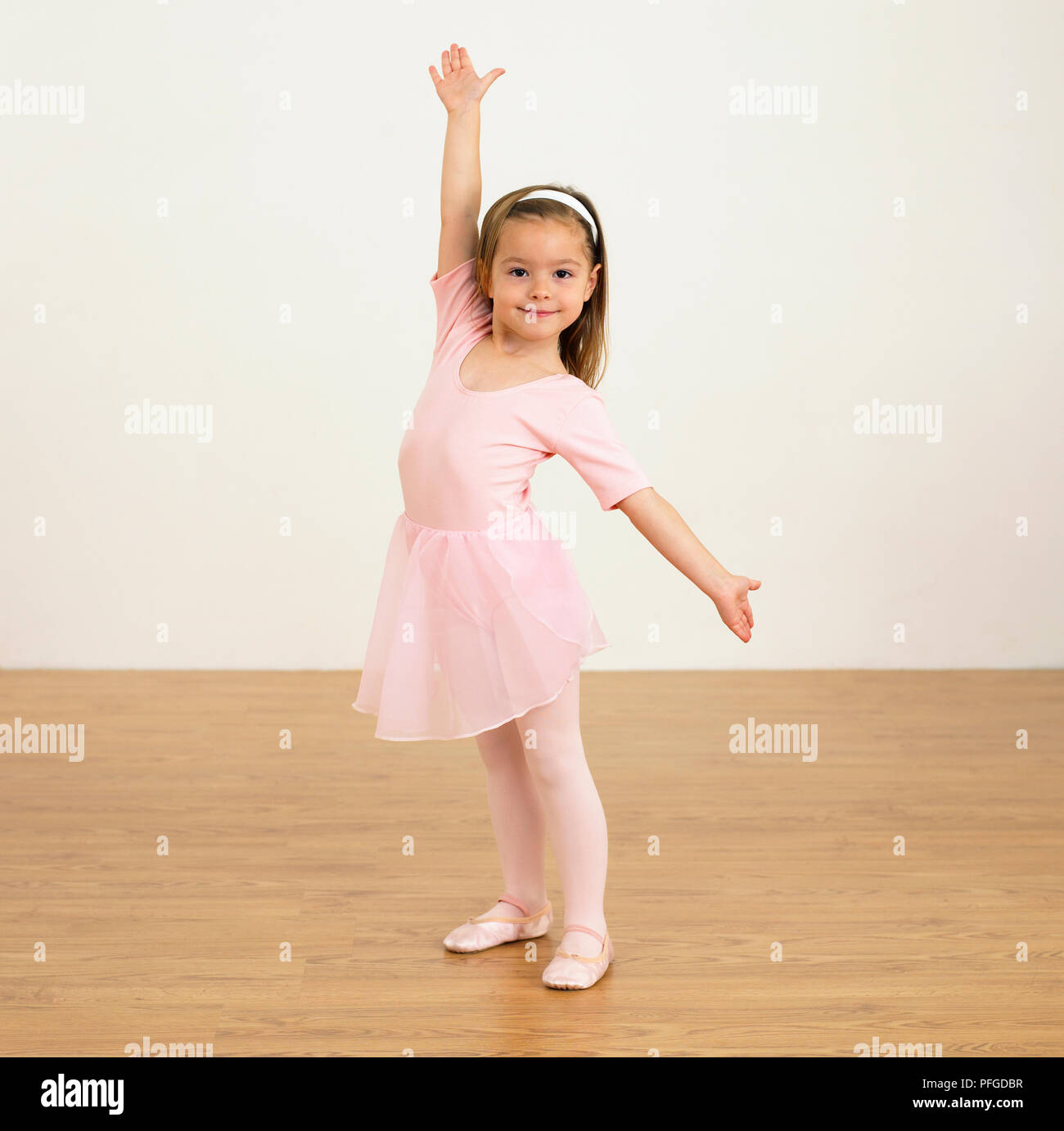 e8b08e80a Girl in ballerina outfit holding one arm up and the other to her ...