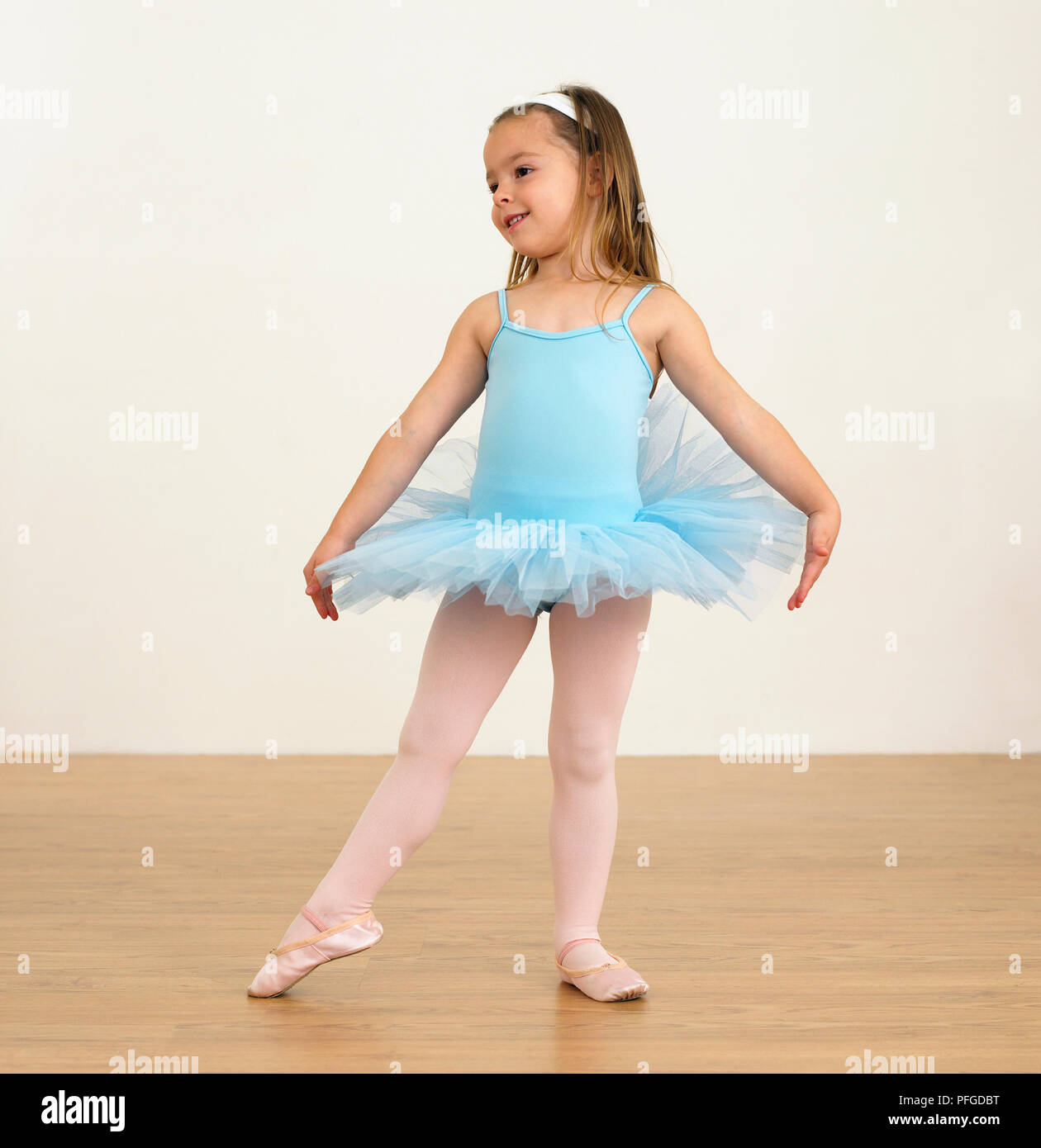 cc2474086aef Girl in blue ballet costume practising first position