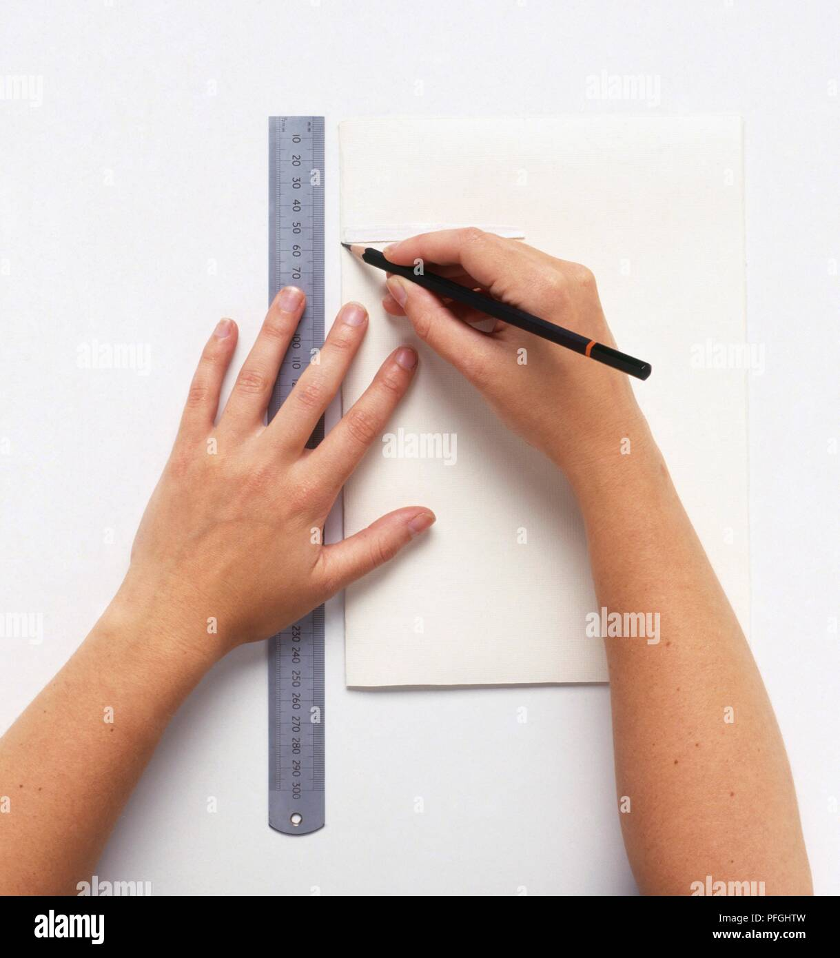 Making a sketchbook, marking width of binding tape using ruler and pencil, close-up - Stock Image