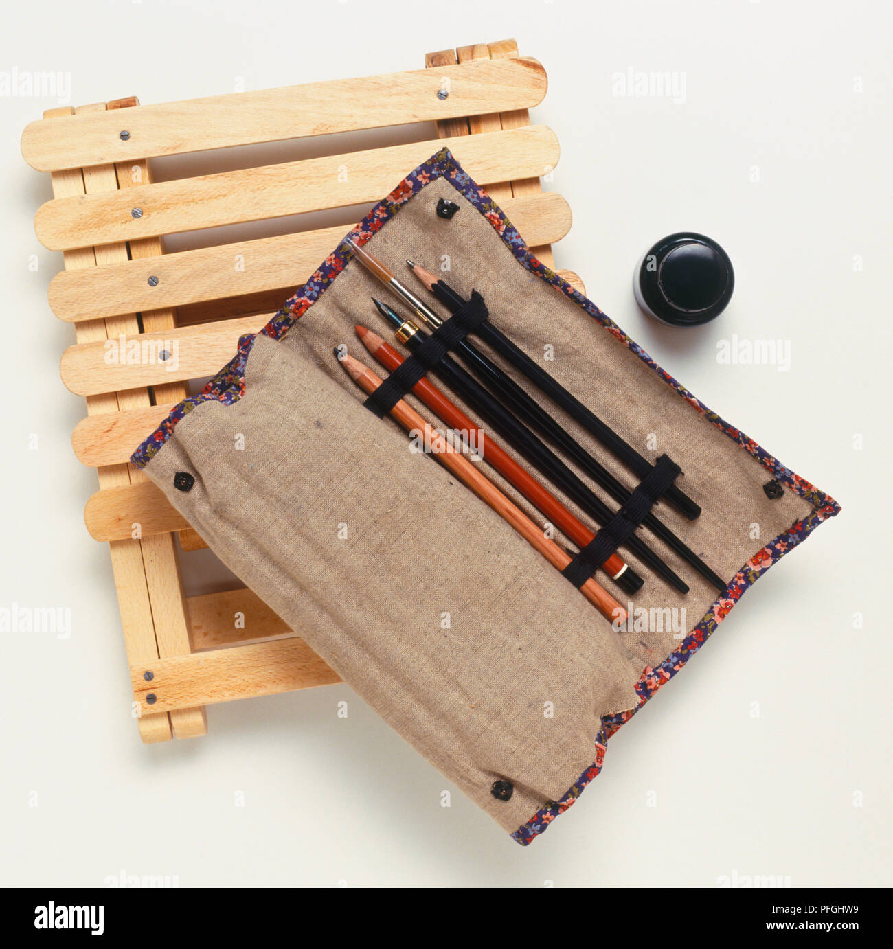 Artist's canvas roll containing pencils, brush and pen, on top of folding wooden stool. - Stock Image