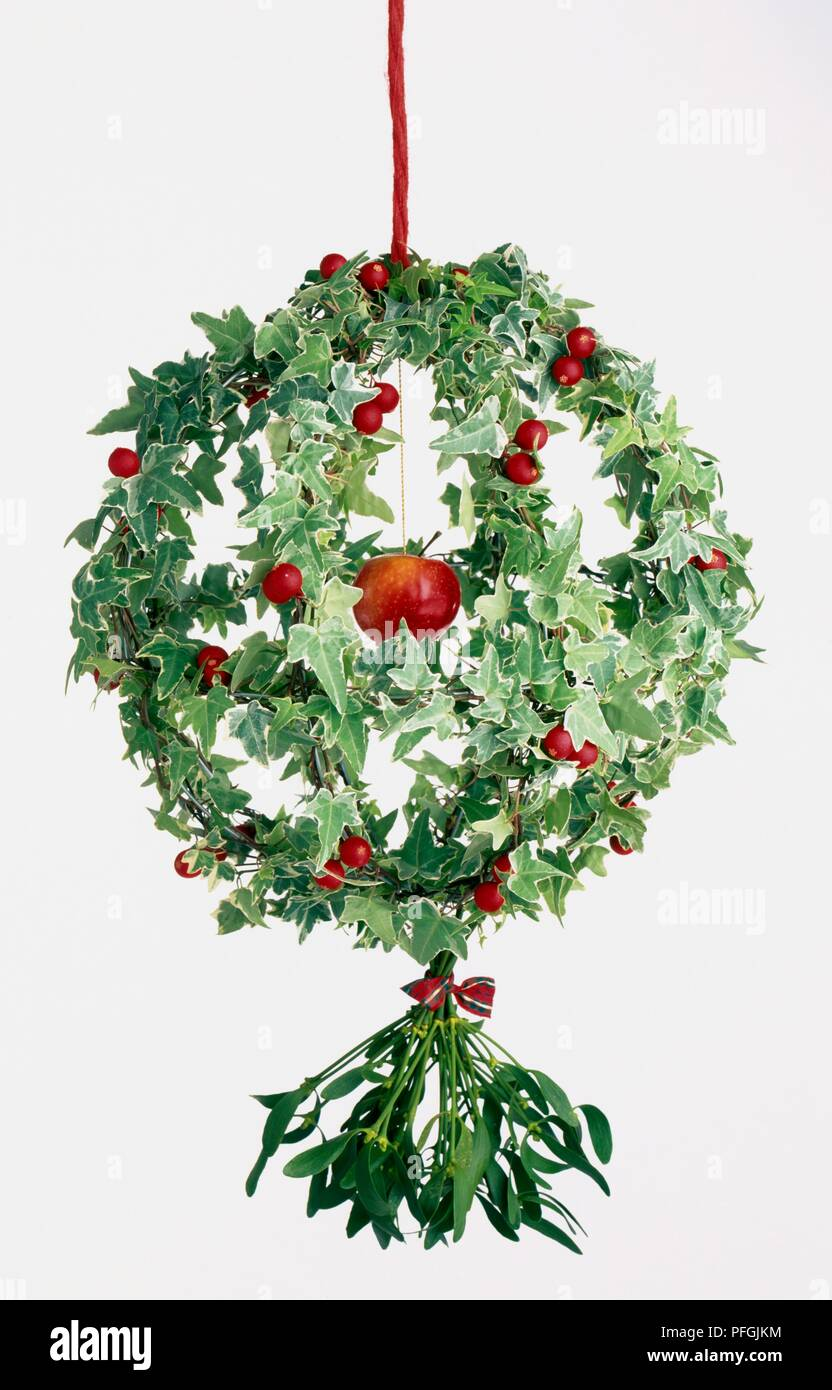 Kissing bough Christmas wreath made from ivy and mistletoe, decorated with red mini baubles and an apple at the centre Stock Photo