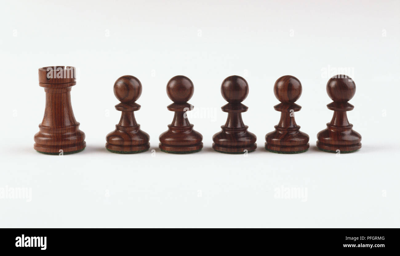 Six wooden chess pieces, a rook and five pawns, close up. - Stock Photo
