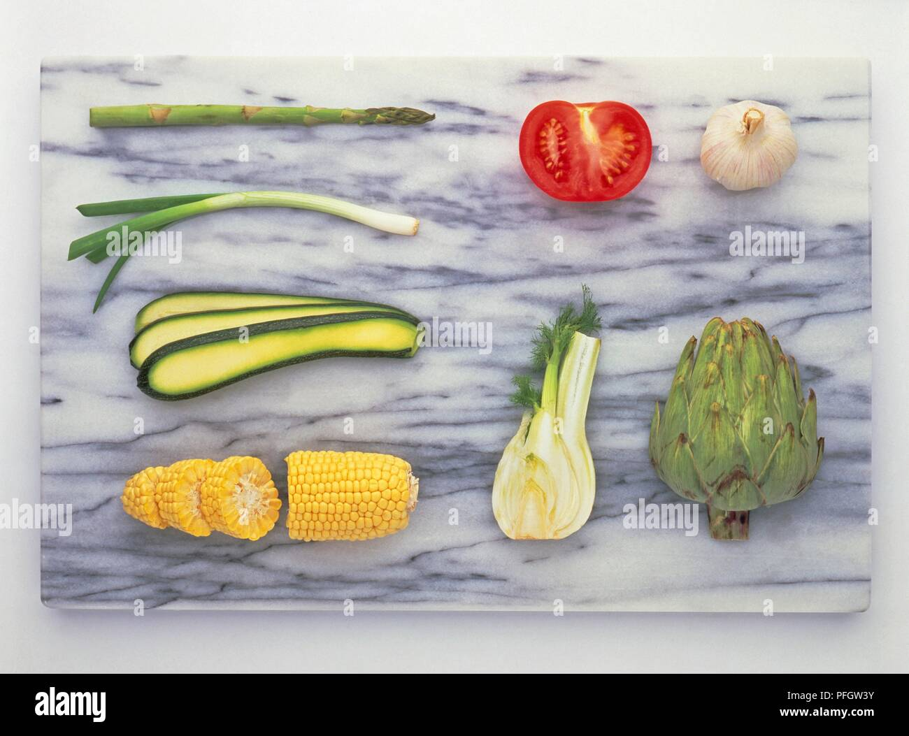 Various vegetables on marble chopping board, asparagus, spring onion, courgette, sweetcorn, fennel, artichoke, tomato, garlic Stock Photo