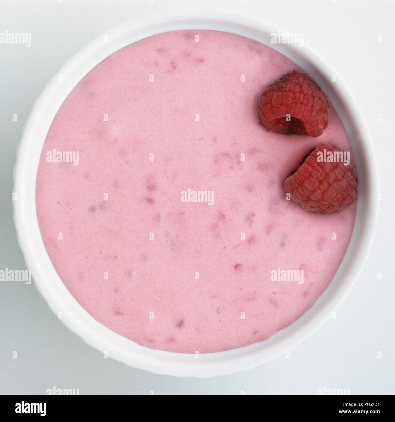 Four raspberry fools, made from whipped cream and pureed fruit, topped with fresh raspberries in four round white ramekins. - Stock Image