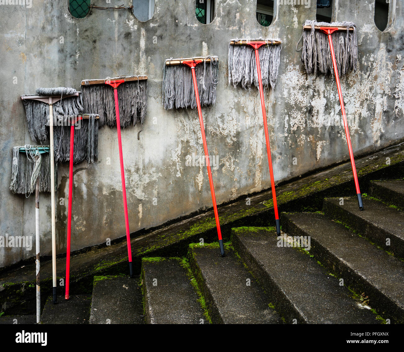 Several mops against a dirty old wall : spring cleaning concept - Stock Image