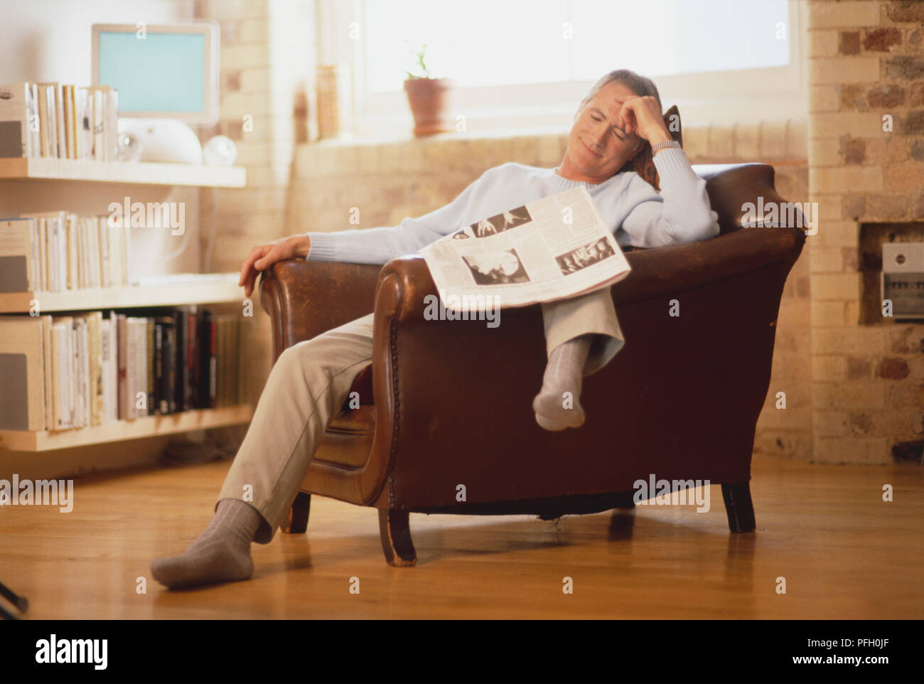 Mature man sitting in brown leather armchair, one leg over chair arm ...