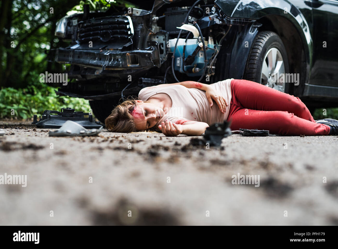 Young Injured Woman Lying In Blood On The Road Unconscious A Car