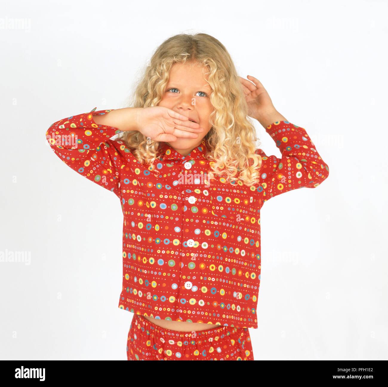 Girl in pyjamas yawning - Stock Image