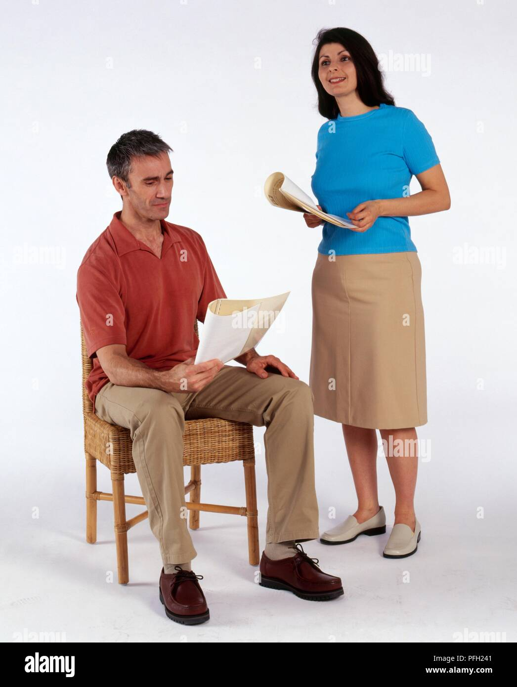 Man and woman rehearsing lines from scripts - Stock Image