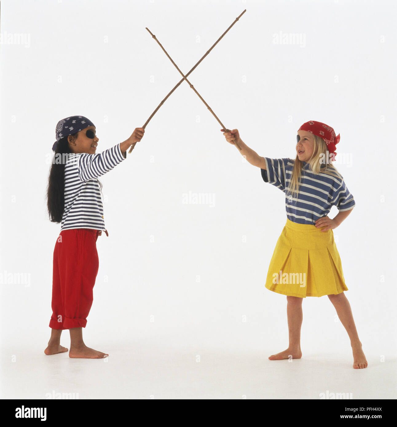 Two girls in pirate costumes crossing twig 'swords', side view - Stock Image