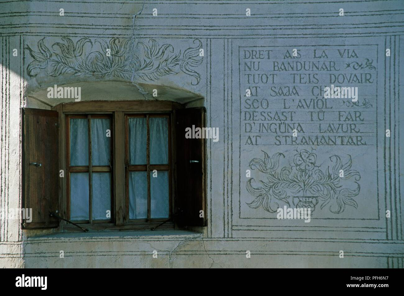 Switzerland, Graubunden Canton, Lower Engadine, Guarda, sgraffito decoration and inscription in Romansh on the facade of a house - Stock Image