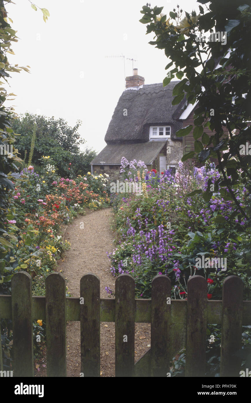 Garden path surrounded on both sides by colourful flower beds, leading up to a cottage, wooden gate in foreground - Stock Image