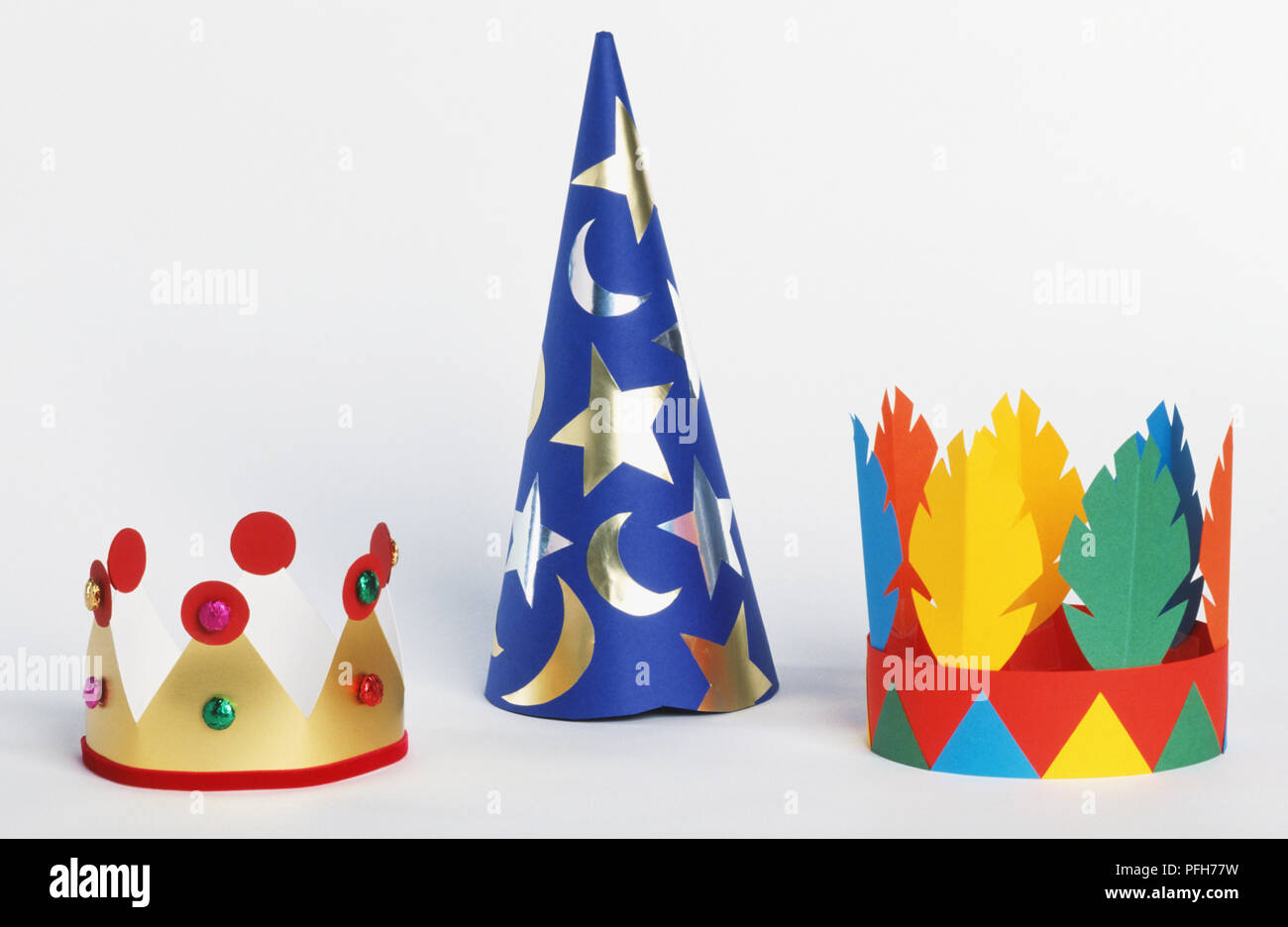 Paper gold crown, wizard hat and feather crown - Stock Image
