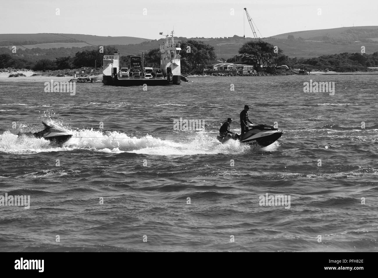 Sandbanks, Dorset, England - June 02 2018: Black and white shot of a jet ski crossing Poole Harbour in Dorset, with the chain link ferry in the backgr - Stock Image