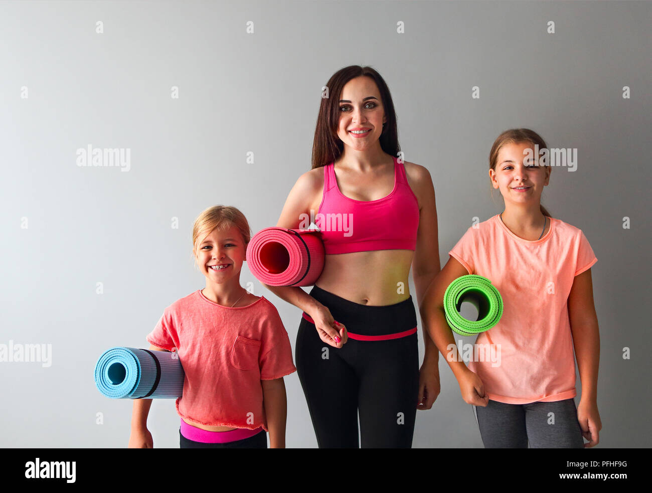 Young woman having fun with kids doing yoga  Family sport