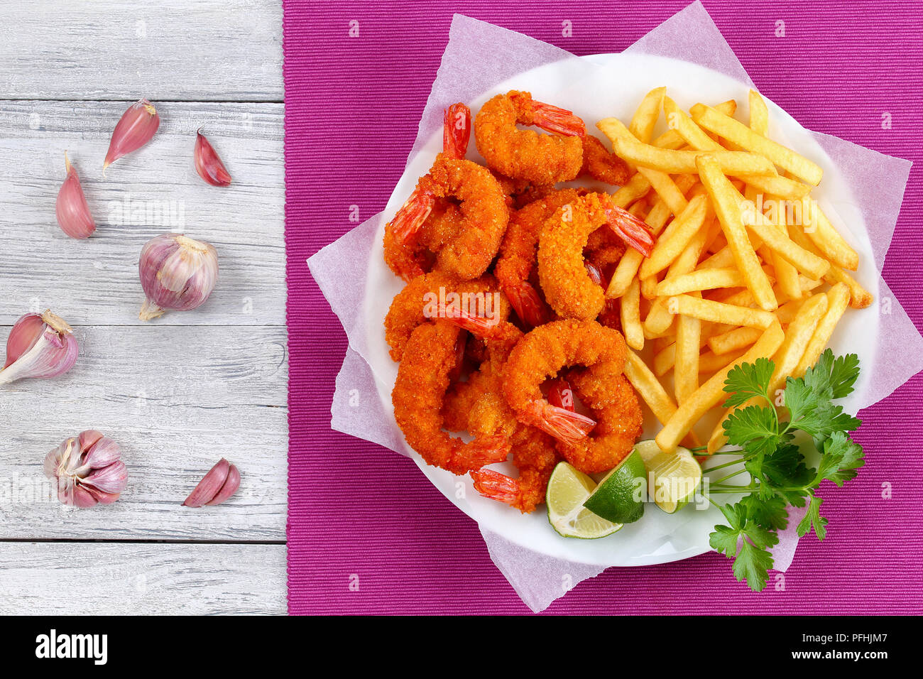 delicious light and crispy crunchy parmesan breaded Fried Shrimps with lime wedges, french fries and parsley on white plate on wooden table, garlic cl Stock Photo