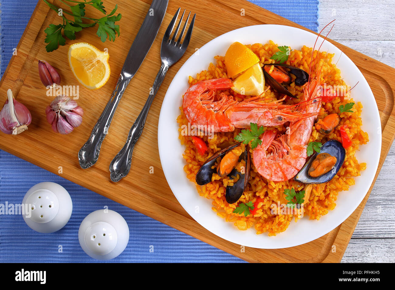 portion of gourmet seafood valencia paella with king prawns, mussels on savory creamy saffron rice with spices and lemon wedges on plate, on wooden ch - Stock Image