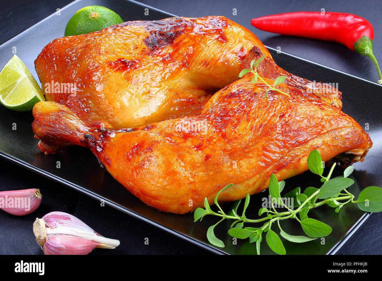 delicious roasted chicken legs with crispy golden brown skin with lemon slices and fresh green thyme leaves on black plate on slate tray, view from ab - Stock Image