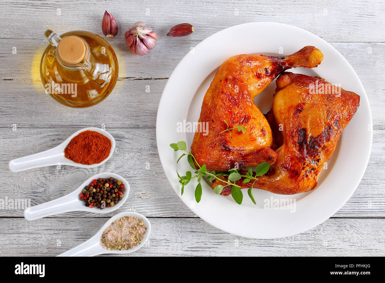 delicious roasted chicken leg quarters with crispy golden brown skin with fresh green thyme leaves on white plate, on wooden table with spices and bot - Stock Image
