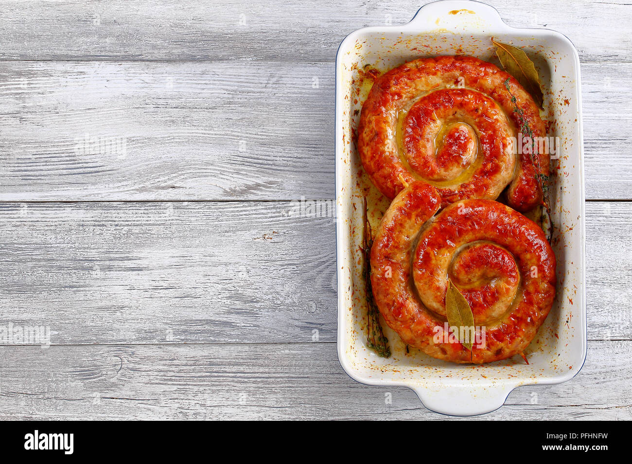 delicious german Bratwurst - round fried sausages on wooden skewers in roasting dish on old rustic wooden table, view from above, blank space left - Stock Image