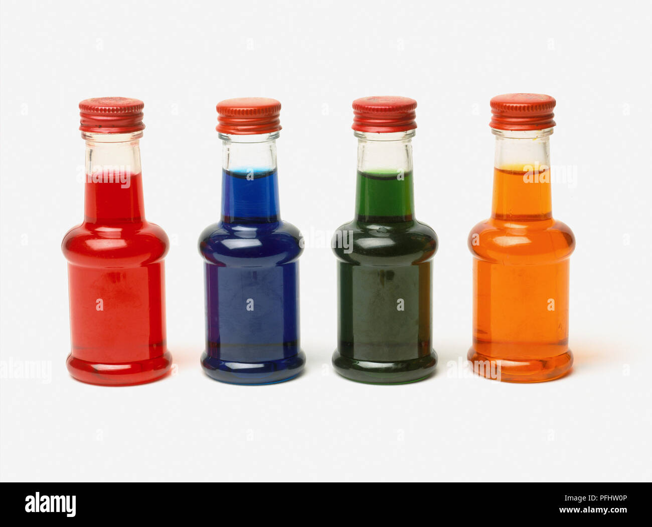 Bottles of red, blue, green and yellow food colouring, close up ...