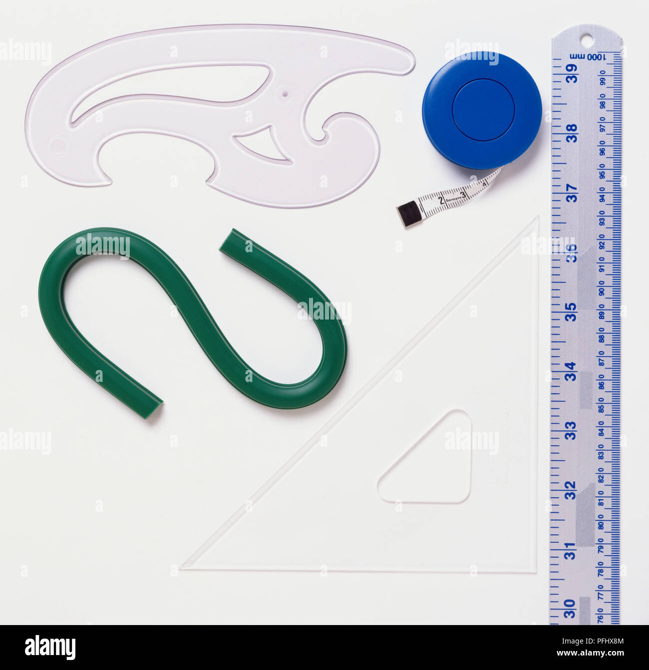 Ruler, retractable tape measure, French curve, flexible curve and set square. - Stock Image