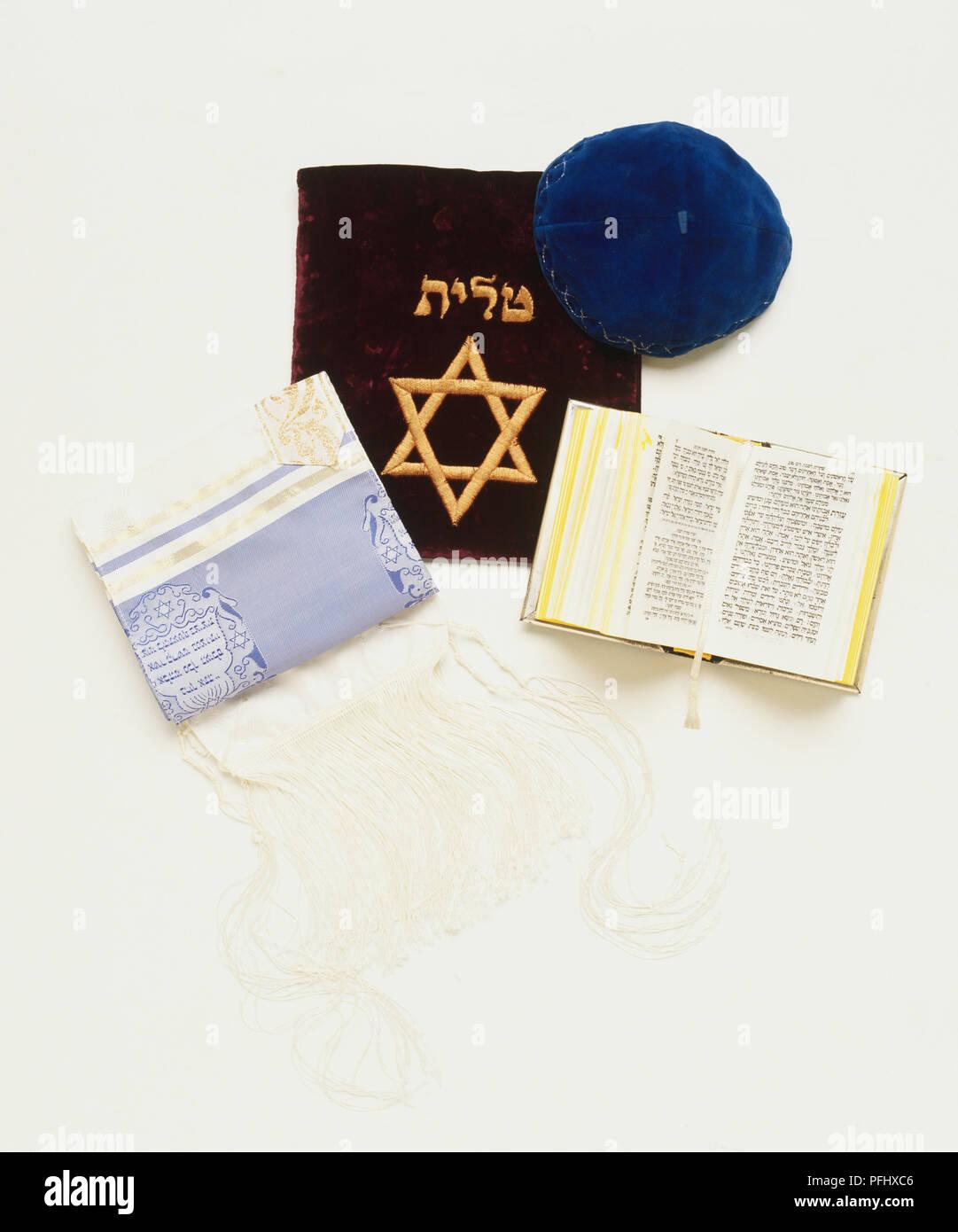 Blue skull-cap, Jewish prayer shawl and embroidered shawl bag, Hebrew prayer book, front view. - Stock Image