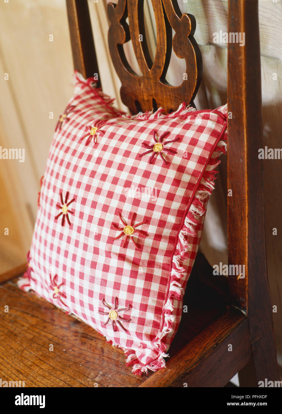 Red And White Checkered Cushion On A Wooden Chair Close Up Stock