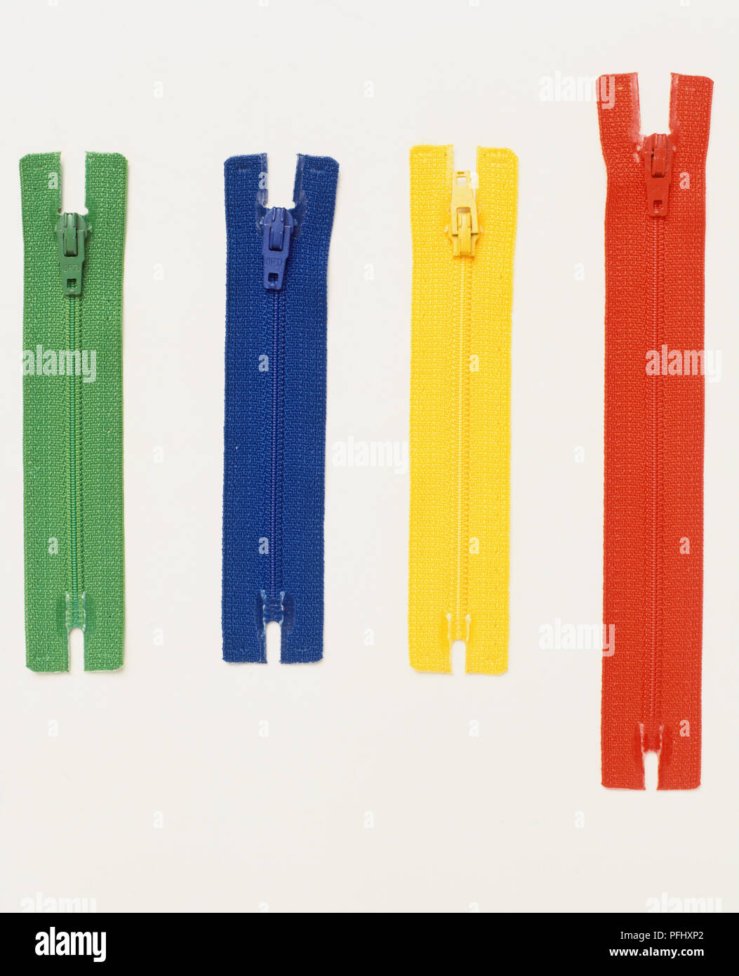 Red, yellow, green and blue zippers, close up. - Stock Image