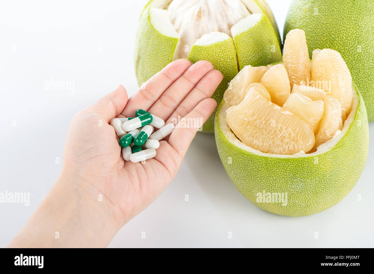 fresh and peeled pomelo(shaddock), grapefruit with drug, concept of drug interatcions - Stock Image