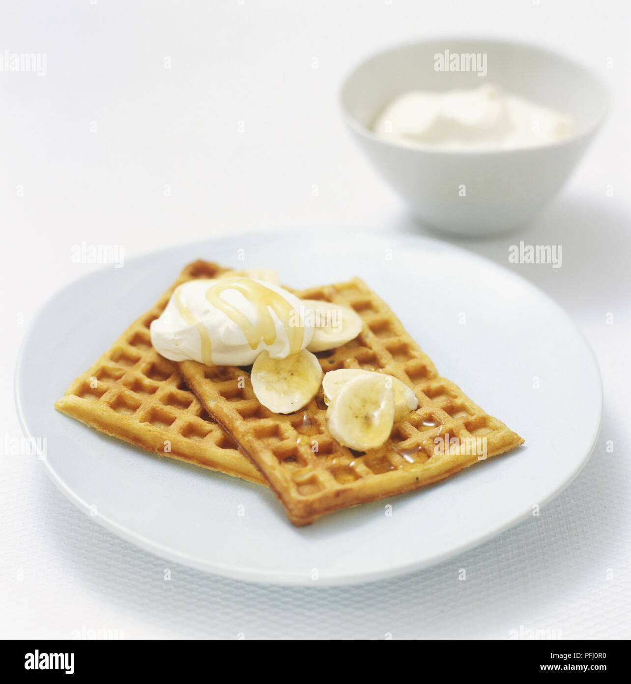 Belgian waffles served with whipped cream, banana slices and golden syrup, high angle view - Stock Image