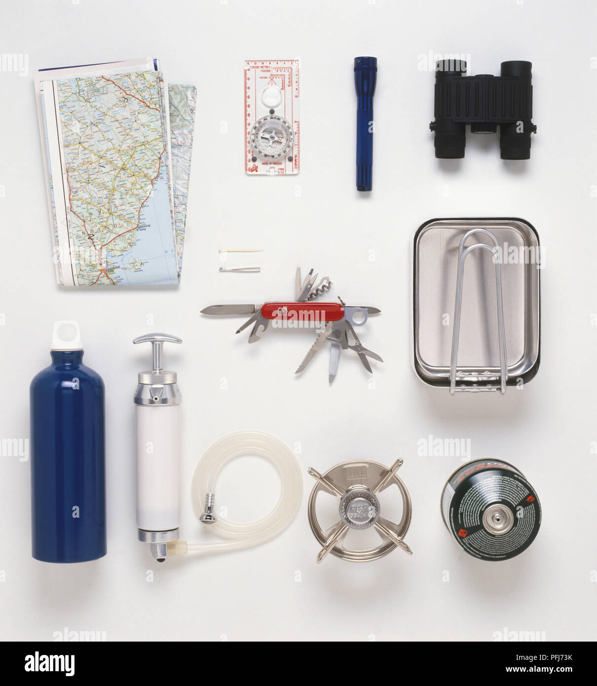 Personal camp kit, map, compass, torch, binoculars, mess tin, swiss army knife, water purifier, stove and fuel - Stock Image