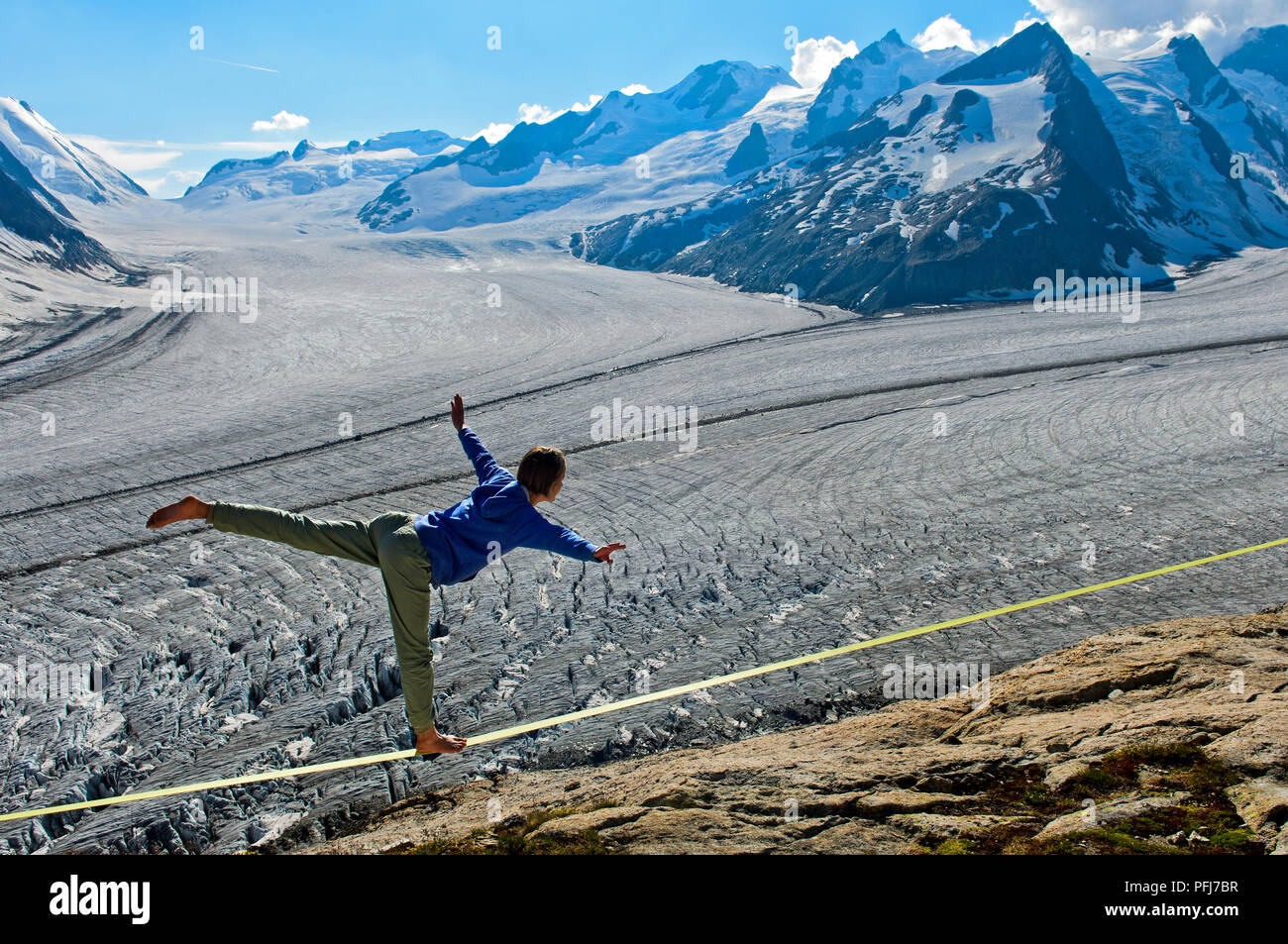 Young woman is balancing on the slackline at the Konkordia Hut over the glacier ice at Konkordiaplatz, Bernese Alps, Valais, Switzerland - Stock Image
