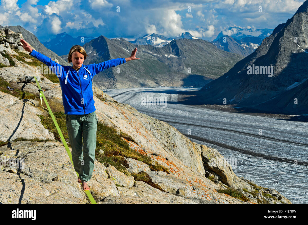 Young woman is balancing on the slackline at the Konkordia Hut over the Aletsch Glacier, Bernese Alps, Valais, Switzerland - Stock Image